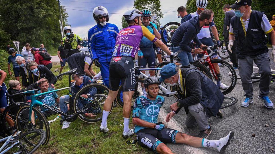 Tour e France: Verletzte Fahrer sitzen nach einem Massensturz auf dem Boden