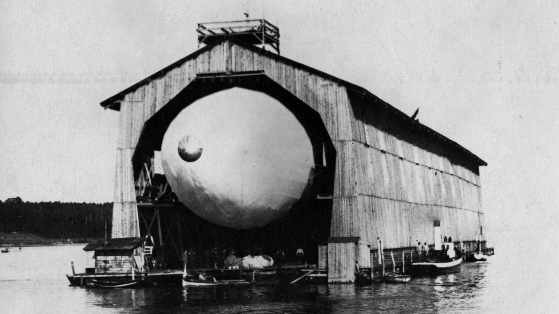 """2. Juli 1900: Der erste """"Zeppelin"""" hebt ab  Ferdinand Graf von Zeppelin will Ende des 19. Jahrhunderts Luftschiffe entwickeln und bauen. Bei der Umsetzung hauptsächlich auf sich allein gestellt, finanziert er sein Unternehmen selbst. 1899 beginnt die Montage des ersten Prototyps, der LZ 1, in einer schwimmenden Montagehalle auf dem Bodensee. Am 2. Juli hebt die LZ 1 das erste Mal ab, unter den Augen von rund 12.000 Zuschauer:innen. Nach 18 Minuten Flug muss der """"Zeppelin"""" aber auf dem Wasser notlanden. Graf Zeppelins Gelder sind danach erschöpft und schließlich musser seine Gesellschaft zum Baum von Luftschiffen auflösen. Fünf Jahre später kann Zeppelin mit neuen Geldern seine Idee weiterentwickeln."""