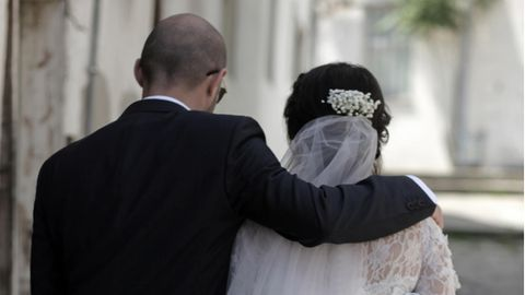 Ein Hochzeitsgast legt tröstend den Arm um die Braut