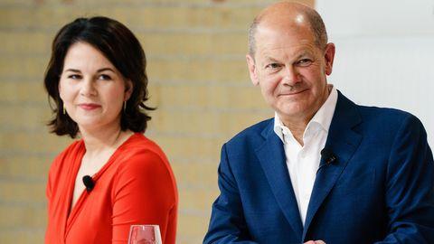 Annalena Baerbock im roten Kleid und Olaf Scholz im blauen Anzug