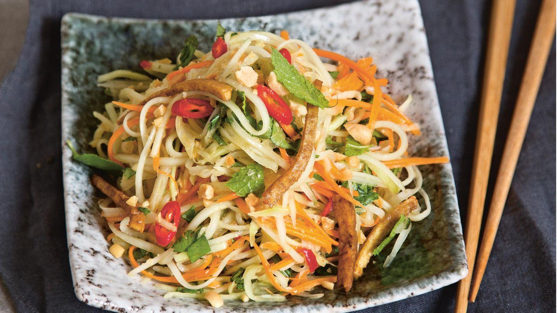 Vietnamesischer grüner Papayasalat      Zutaten: Papayasalat:½ grüne Papaya (ca. 200 g), 1 große Karotte (ca. 100 g), 1 Handvoll vietnamesische Kräuter (z.B. Koriandergrün, Minze, Thaibasilikum), 3 EL geröstete Erdnusskerne, 1 Portion klassische Dip-Sauce, 2 TL geröstetes Sesamöl, 100 g Naturtofu, 1 EL Bratöl (z.B. Sojaöl), 1–2 EL Sojasauce  Klassische Dip-Sauce:10 g Zucker, 2 EL »No-Fish-Sauce« alternativ Sojasauce,2 EL frisch gepresster Limettensaft, ½–1 kleine rote Chilischote, 1 Knoblauchzehe  Außerdem: 1 Handvoll vietnamesische Kräuter 2 EL Röstschalotten      Zubereitung:Die Papaya und die Karotte schälen und mit einem Julienneschneider in feine Streifen schneiden. Die Kräuter waschen und Blättchen grob hacken. Die Erdnüsse mittelfein hacken. Die Gemüsestreifen mit den Kräutern und 2 EL Erdnüssen in eine Salatschüssel geben und leicht durchkneten. Die Dip-Sauce (Für die klassische Dip-Sauce den Zucker in einem Schälchen mit 30 ml heißem Wasser übergießen und unter Rühren auflösen. Mit der »No-Fish-Sauce« und dem Limettensaft verrühren. Die Chilischote putzen, auf Wunsch entkernen, fein würfeln und zugeben. Den Knoblauch abziehen, fein würfeln und ebenfalls zugeben. Die Sauce mindestens 15 Minuten ziehen lassen – am besten schmeckt sie, wenn sie über Nacht im Kühlschrank durchzieht.) mit dem Sesamöl vermischen, als Dressing unter den Salat heben und diesen mindestens 15 Minuten ziehen lassen. Inzwischen den Tofu in feine Streifen schneiden. Das Bratöl in einer mittelgroßen Pfanne erhitzen. Den Tofu darin unter gelegentlichem Rühren bei mittlerer Temperatur in etwa 7–10 Minuten goldbraun braten. Die Sojasauce zugeben und unter Rühren einkochen lassen. Den Salat nochmal durchmischen und auf zwei Tellern anrichten. Mit Tofustreifen, übrigen Erdnüssen, Kräutern und Röstschalotten garniert servieren.