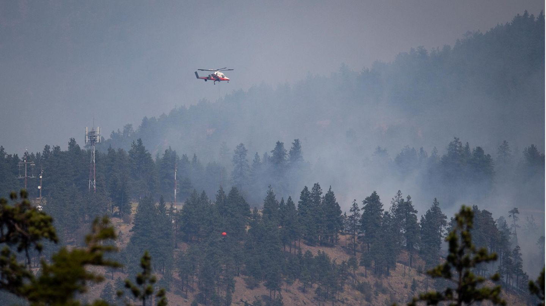 Ein rot-weiß lackierter Hubschrauber fliegt über einen bewaldeten Hang, während zwischen den Nadelbäumen Rauch aufsteigt