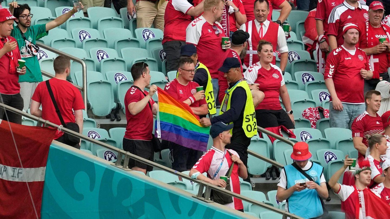 Ordner nehmen einem Fan im Stadion seine Regenbogen-Flagge ab