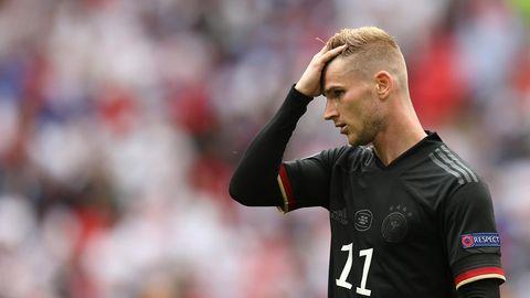 Im schwarzen DFB-Dress steht Timo Werner auf dem Platz und streicht sich mit Rechts durch sein blondes Haar
