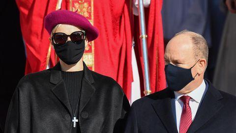 Eine elegant gekleidete Frau mit weinroter Baskenmütze, Sonnenbrille und schwarzem Mundschutz steht neben einem kleineren Mann