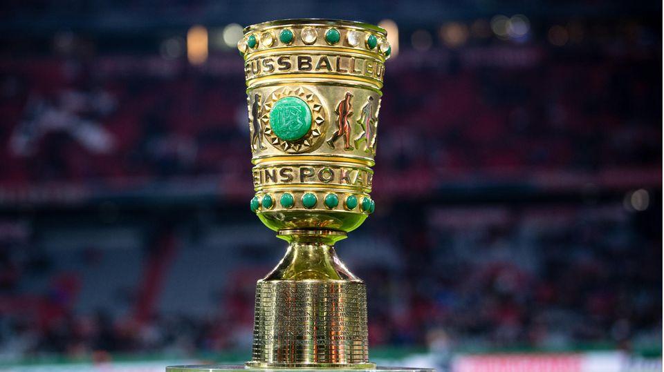 Auf einem Sockel in einem Fußball-Stadion steht er goldene DFB-Pokal mit grünen Ziersteinen