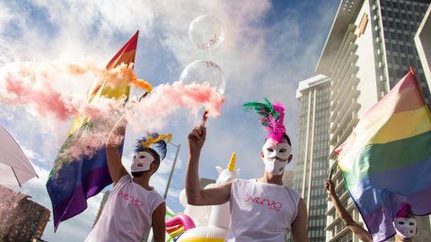 Bei einer Pride-Parade marschieren bunt gekleidete Menschen mit Masken und schwenken die Regenbogen-Flagge