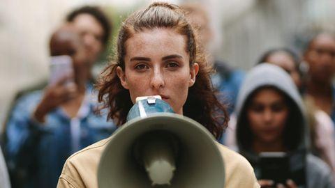 Eine junge Frau der Generation Z steht mit einem Megaphon auf der Straße.