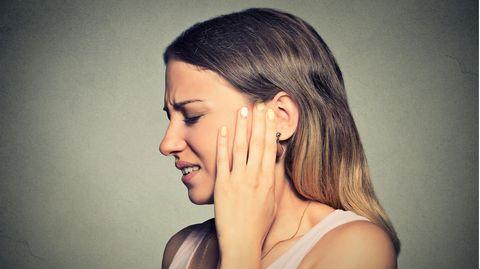 Eine junge Frau hat Ohrenschmerzen