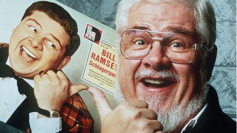 Bill Ramsey hält eine seiner alten Platten in der Hand und lacht in die Kamera