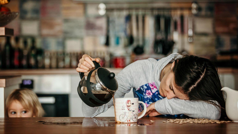 Eine müde Mutter schenkt sich mit dem Kopf auf den Tisch gelegt Kaffee ein