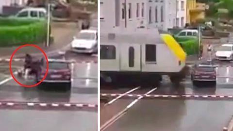Eine Frau rettet sich aus dem Auto, Sekunden bevor ein Zug ihr Auto überrollt.
