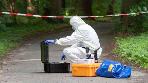 Ein Mitarbeiter der Spurensicherung trägt einen weißen Schutzanzug und nimmt Material aus einem Koffer