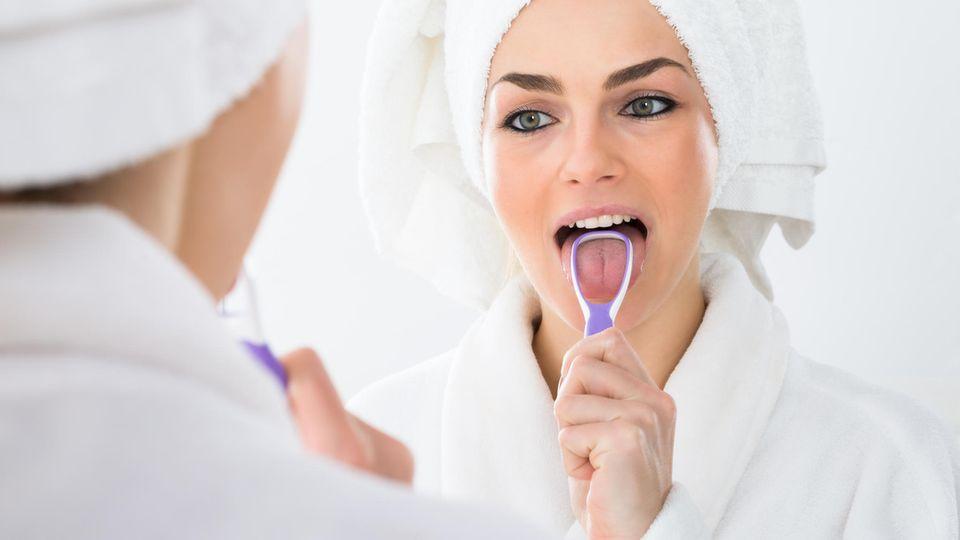 Eine Frau wenden einen Zungenschaber an