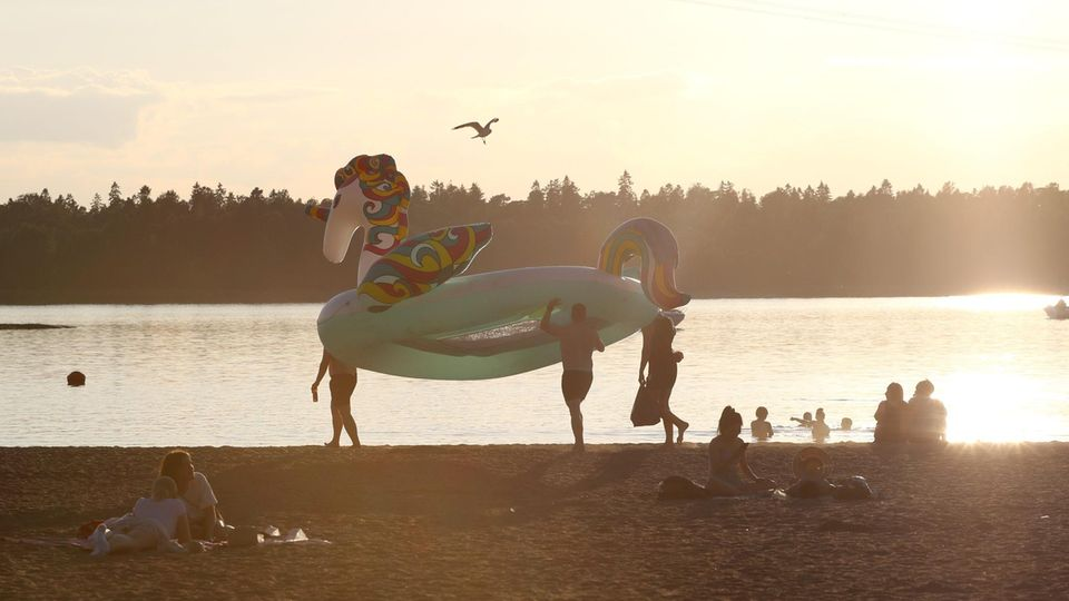 Badegäste tragen ein Schwimmreifen in Form eines Einhorns über den Strand während die Sonne untergeht