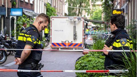 Hinter rot-weißem Absperrband stehen zwei Polizisten in schwarzen Uniformen mit neongelben Streifen