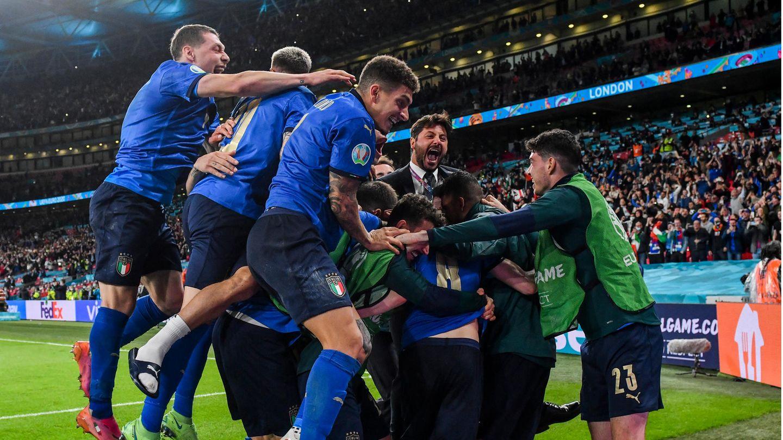 Eine Gruppe Fußballer in blauem Dress jubelt gemeinsam in einer Traube mit ihrem Trainer im Anzug