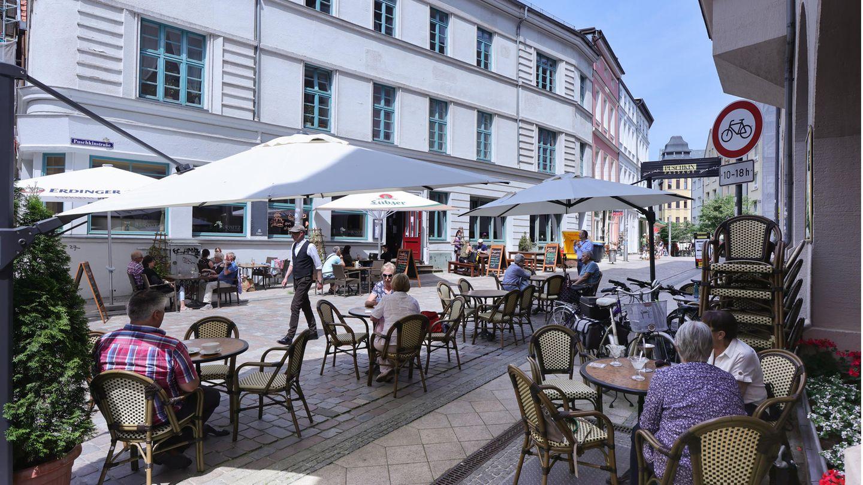 Passanten genießen in einem Straßencafé in Schwerin das sommerlichem Wetter