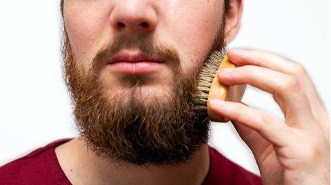Ein Mann bürstet seinen Bart