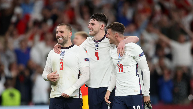 Drei weiße Fußballer in weißen Trikots und dunkelblauen Hosen gehen Arm in Arm und lächelnd über den Platz
