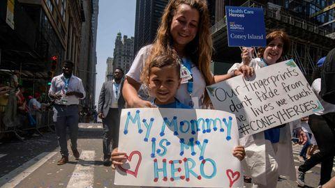 """Ein blonder weißer Junge hält ein Schild, auf dem steht: """"Meine Mama ist meine Heldin"""". Von hinten umarmt ihr eine Frau"""