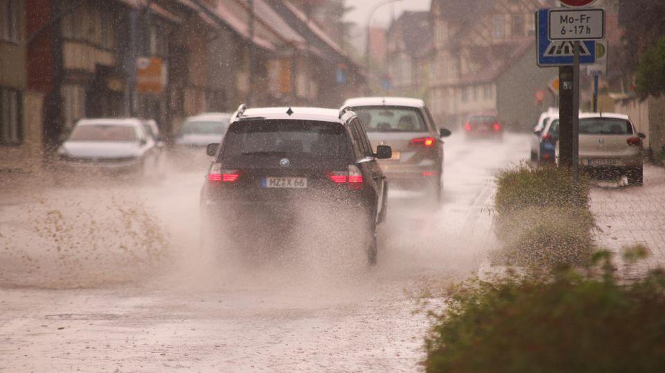 Unwetter im Sommer in Deutschland: Autos fahren durch eine unterspülte Straße.