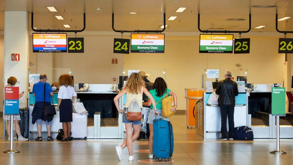 Reisende am Schalterder Fluggesellschaften Lufthansa und Swiss in Faro.