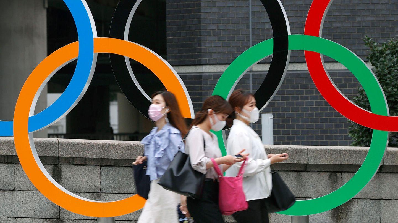 Menschen mit Gesichtsmasken gehen an der Statue der Olympischen Ringe in Tokio (Japan) vorbei