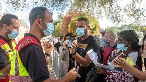 Menschen mit Mund-Nasen-Bedeckung stehen in Lissabon Schlange vor einemCorona-Impfzentrum auf dem Universitätsgelände