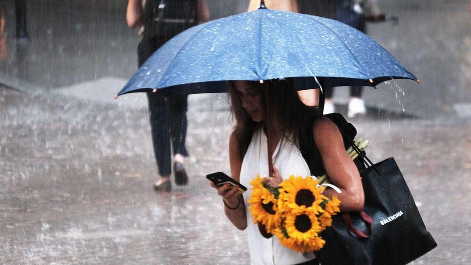 Im strömenden Regen schaut eine weiße Frau in weißem Top unter einem blauen Regenschirm auf ihr Smartphone