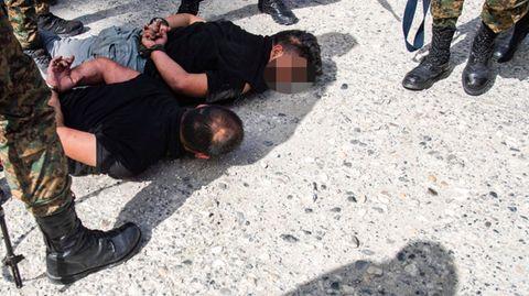 Soldaten in Tarnfleck und mit schwarzen Steifeln stehen um zwei gefesselte, am Boden liegenden Männer herum