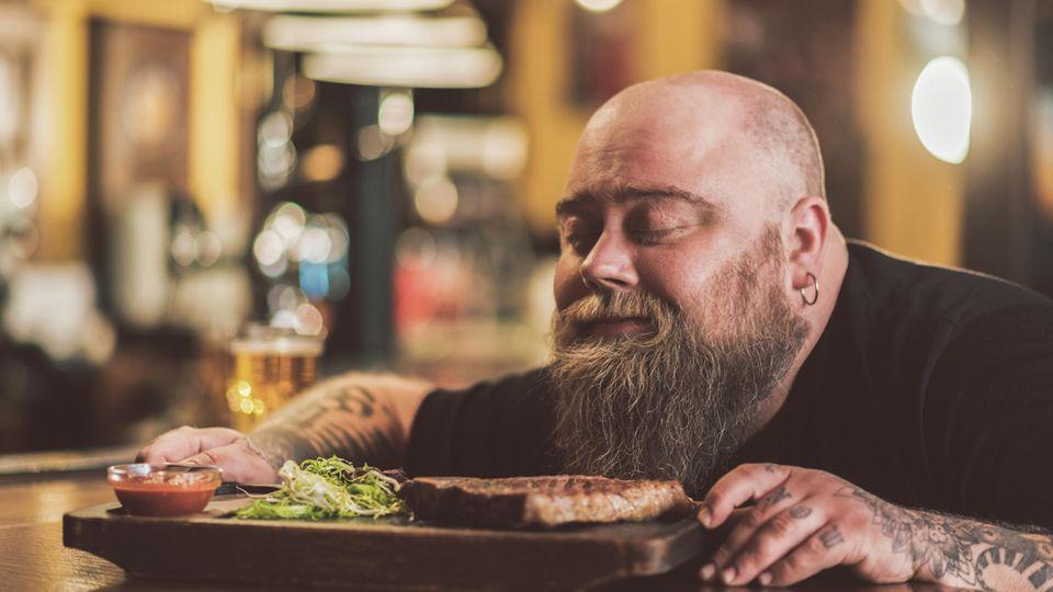 Ein Mann mit Vollbart riecht mit geschlossenen Augen an einem Steak