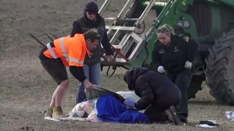 Zwei Männer und zwei Frauen beugen sich über eine blau gekleidete, am Boden liegende Person. Im Hintergrund steht ein Traktor.