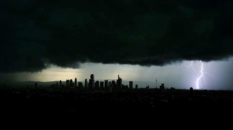 Tiefschwarze Gewitterwolken über einem Stadtpanorama, rechts ist ein Blitz zu sehen
