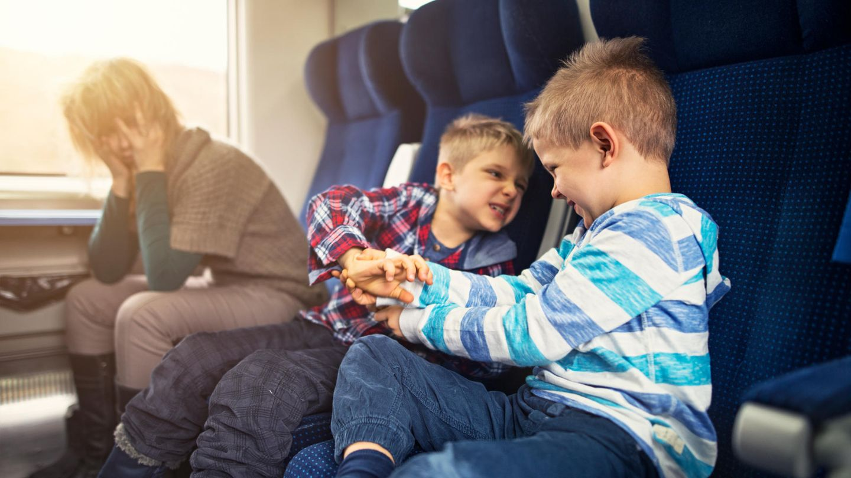 Eine Mutter fährt mit zwei Kindern Zug, die sich streiten. Sie guckt verzweifelt