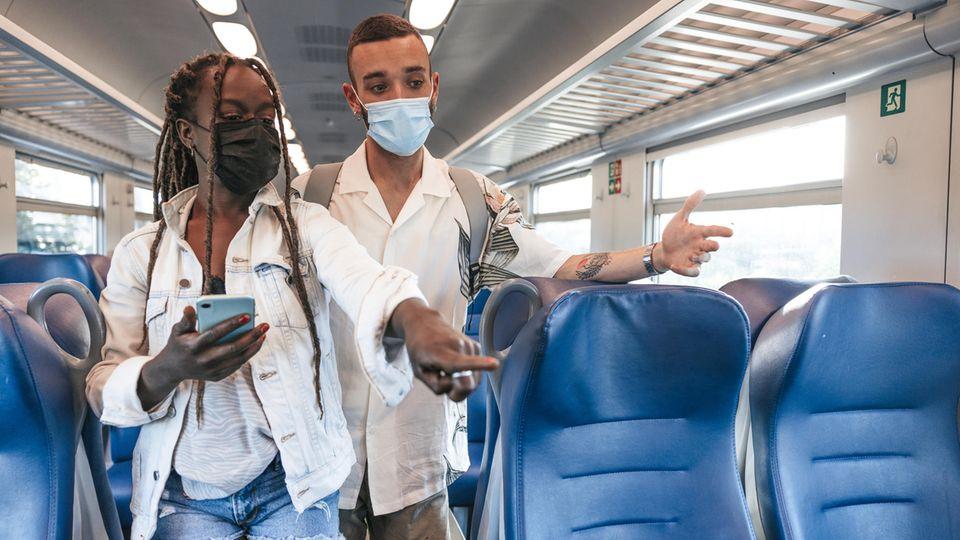 Zwei Menschen suchen im Zug nach einem Platz