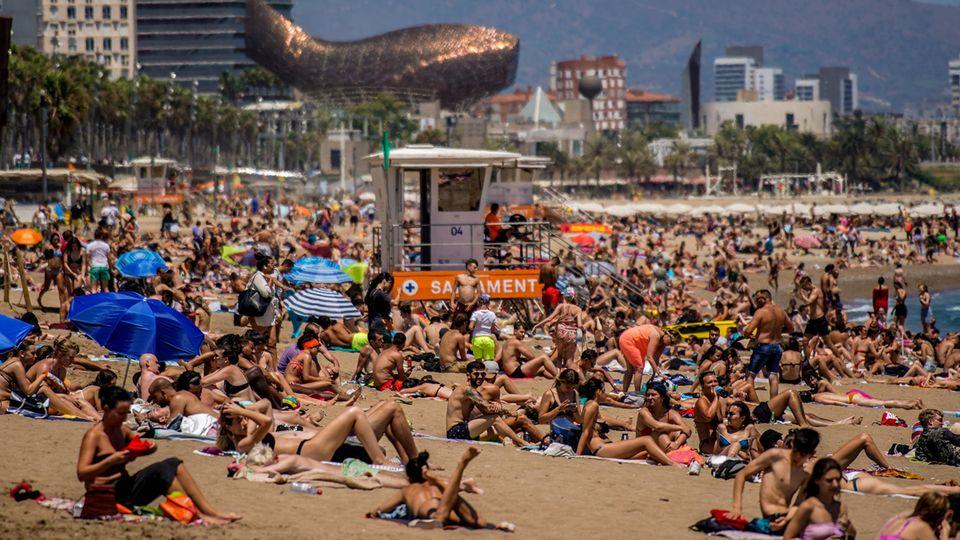 Besucher liegen auf Handtüchern am Strand von Barcelona