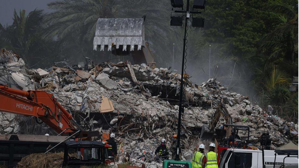 Bagger graben sich durch die Überreste des eingestürzten 12-stöckigen Champlain Towers South in Surfside