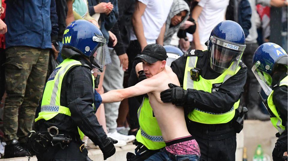 Zwei Polizisten mit Helmen und Schutzkleidung versuchen, einen jungen, weißen Mann mit nacktem Oberkörper festzuhalten