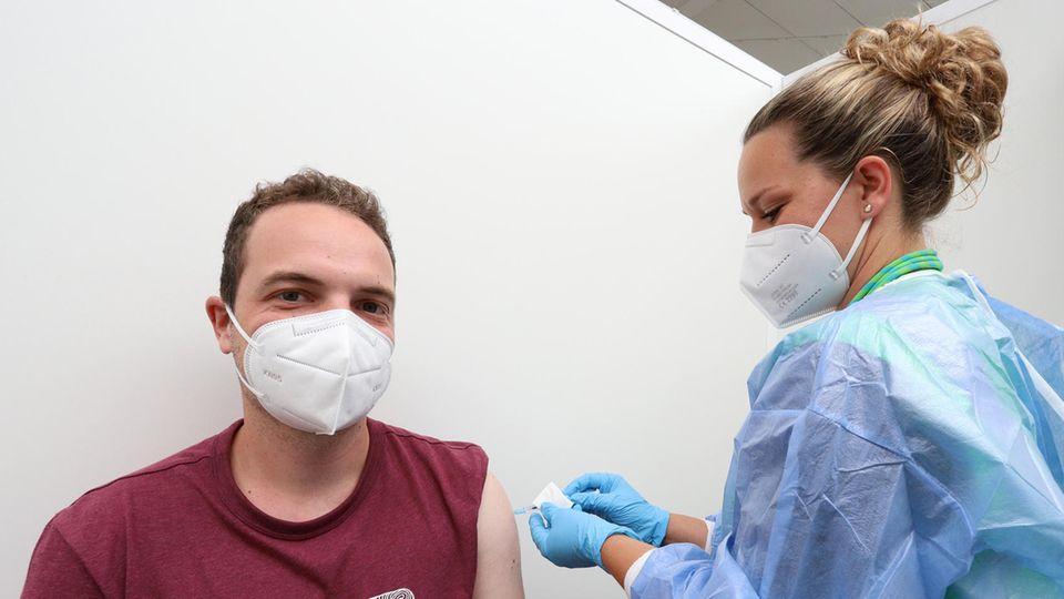 Ein junger weißer Mann mit FFP2-Maske und dunkelrotem T-Shirt, während eine blonde Frau ihm eine Spritze in den Oberarm sticht