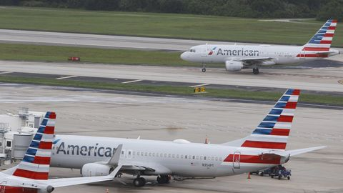 Zwei Flieger von American Airlines, einer steht, einer landet im Hintergrund auf dem Flughafen