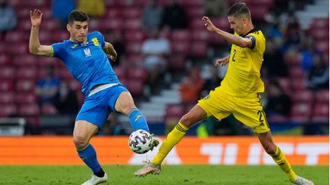 Ukraines Ruslan Malinowskyi und Schwedens Mikael Lustig kämpfen um den Ball