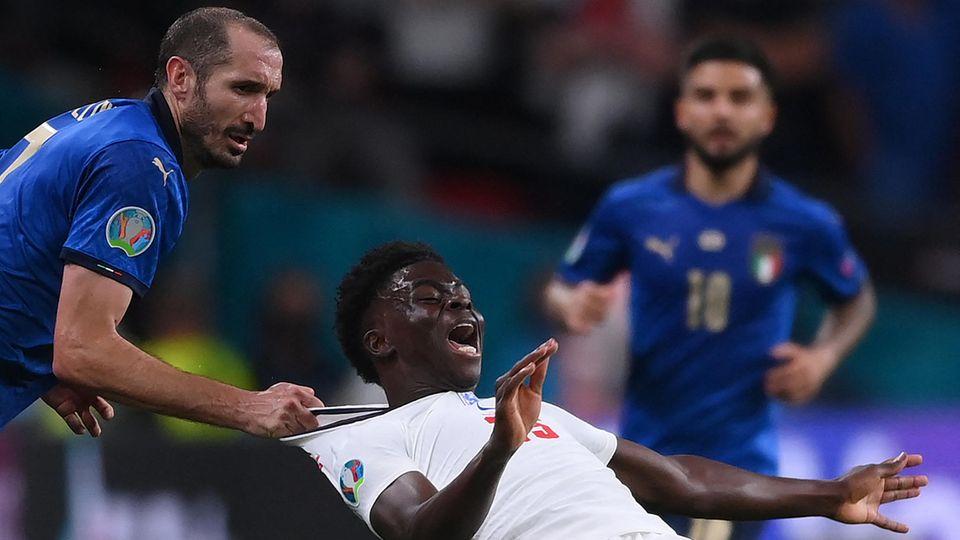 Ein weißer Fußballer im blauen Trikot zieht einen schwarzen Fußballer in weißem Trikot am Kragen nach hinten
