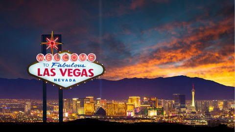 Das Las Vegas-Ortsschild mit der Skyline im Hintergrund bei Dämmerung