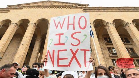 """Mehrere Menschen stehen vor einem Gebäude und demonstrieren, eine Frau hält ein Schild, auf dem """"who is next?"""" steht"""