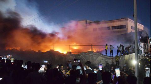 Menschen stehen in der Nacht vor einem brennenden Gebäude