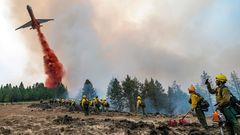 Feuerwehrleute beobachten und filmen mit ihren Handys, wie ein Flugzeug Löschmittel abwirft