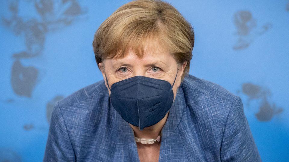 Angela Merkel trägt einen dunkelblauen Mund-Nasen-Schutz