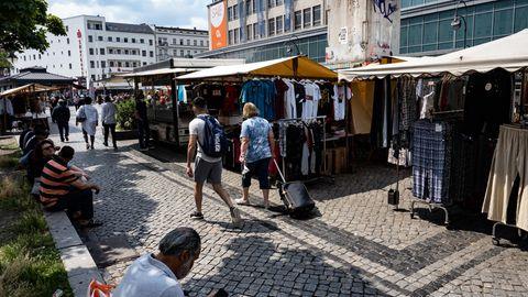 Menschen gehen an den Marktständen auf dem Hermannplatz in Neukölln vorbei
