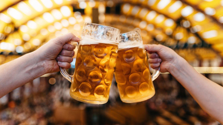 Alkohol Krebs Studie: Menschen stoßen mit Bierkrügen an